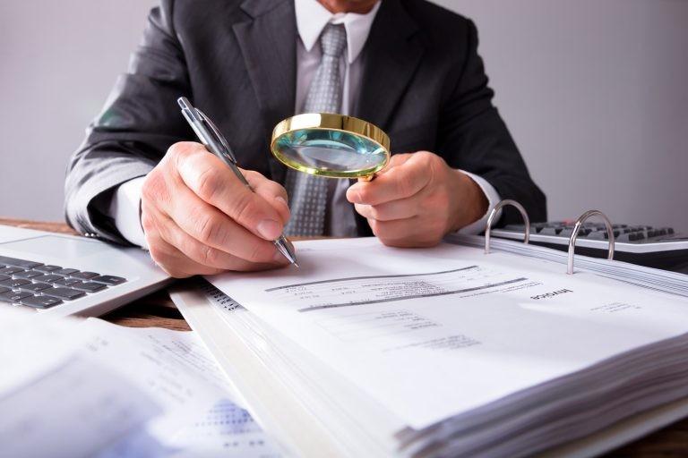 Inspector revisando papeles con una lupa y tomando notas con un bolígrafo.