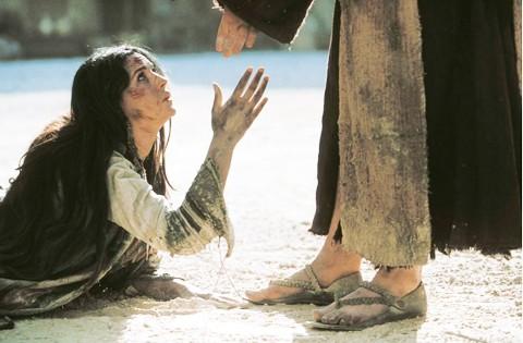Mujer arrodillada pidiendo tolerancia a una persona, esta persona le ofrece la mano.
