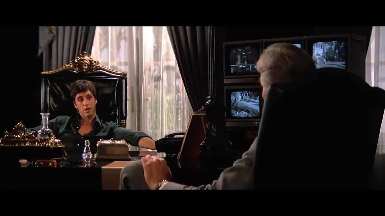 Imagen de una escena emblemática de scarface en la que Tony Montana trajeado y drogado fuma un puro mientras discute sobre sus varias actividades económicas que no son compliant.