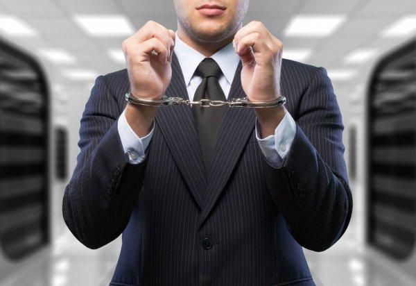 Hombre vestido con traje detenido con esposas puestas. Posiblemente empresario que no ha llevado a cabo el compliance en su empresa.
