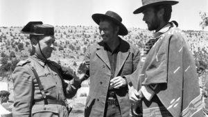Una foto en blanco y negro de un guardia civil hablando con dos hombres en medio del campo.